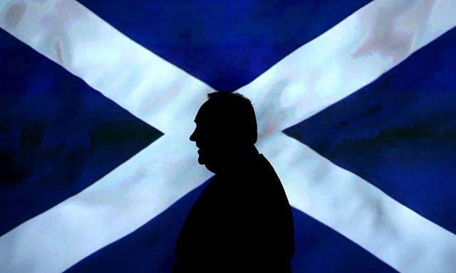 Alex Salmond walking in front of a Saltire